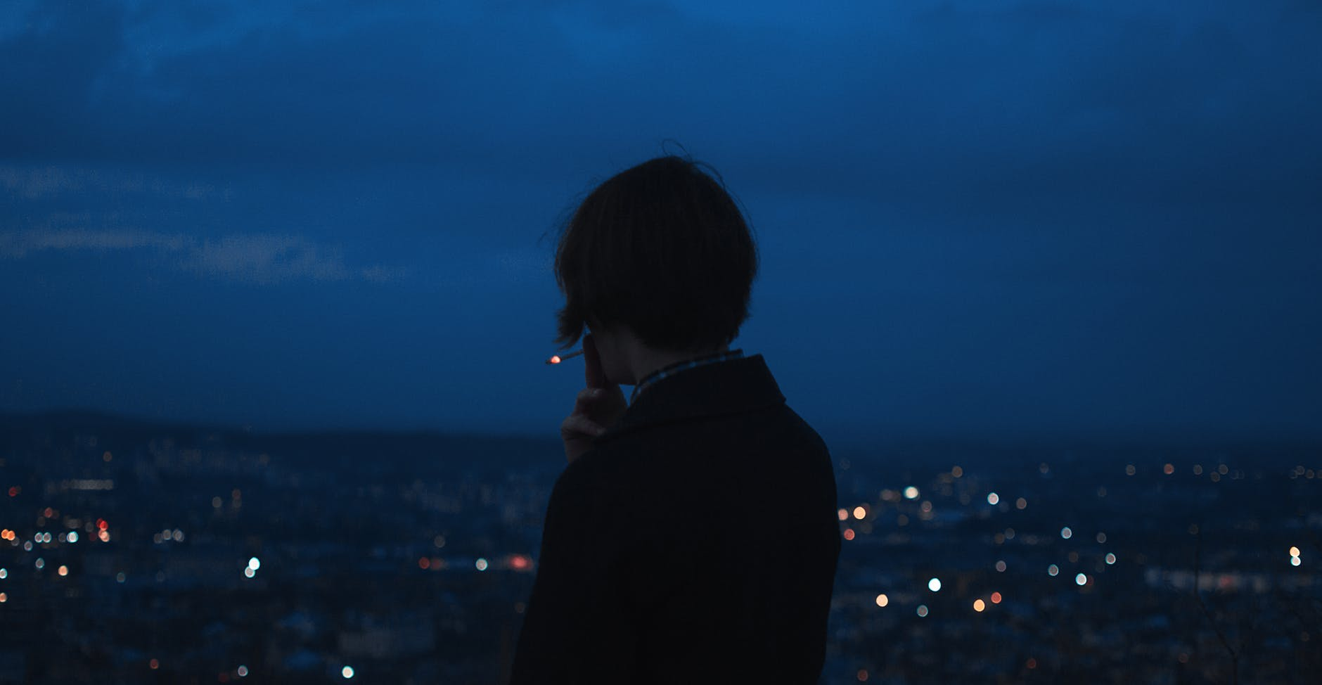 person smoking across city building during nighttime